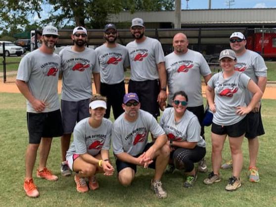Alumni softball team posing together